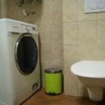 Pračka na 8 kg prádla je umístěna v koupelně.